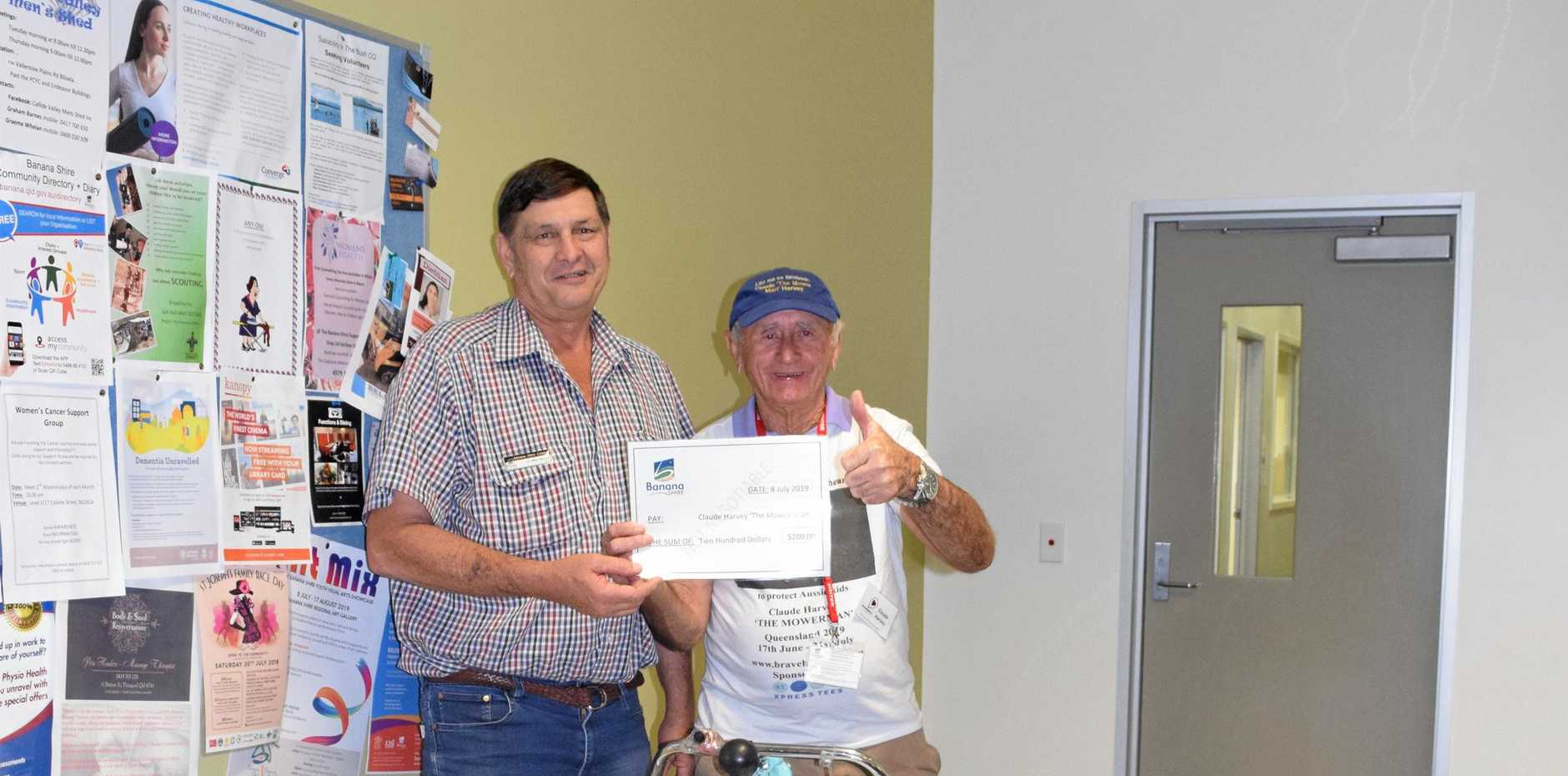 THE MOWER MAN:  Banana Shire Council Mayor Nev Ferrier donated $200 from the council to Claude Harvey's Braveheart cause on Monday.