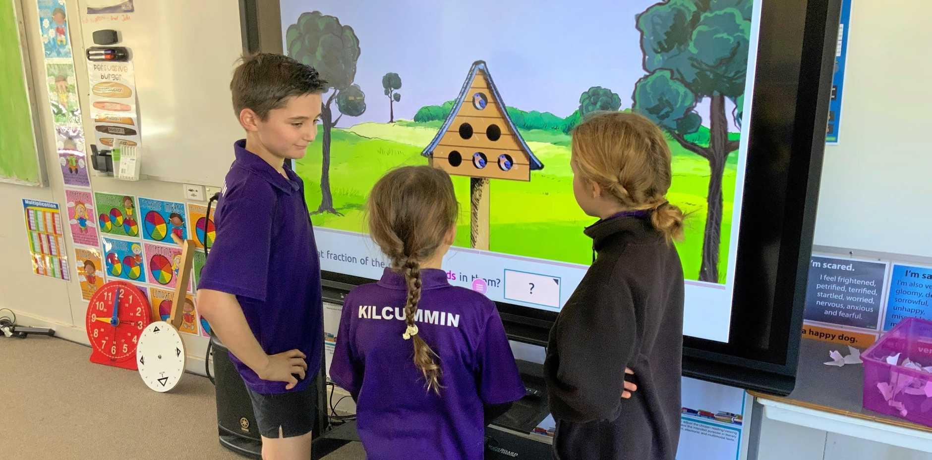 Kilcummin State School students work through Matific activities on an interactive whiteboard.