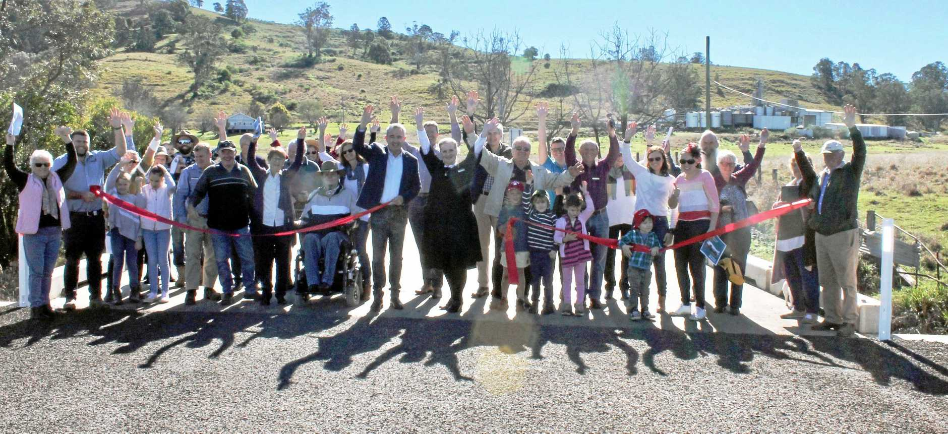 HOORAY, FINALLY: Standing in the centre, Kevin Hogan MP and Kyogle mayor Danielle Mulholland celebrate the opening of Culmaran Creek Rd with residents and business owners.
