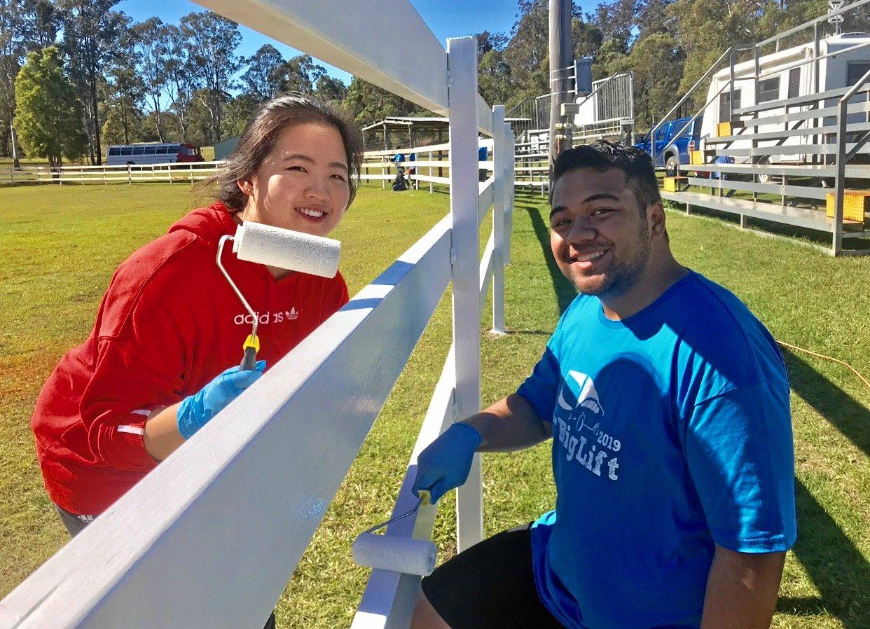 Big Lift for the Blackbutt Show-grounds: Big Lift volunteers Jonathon Maven and Heeji Seo busy painting the fencing of the show-grounds main arena.