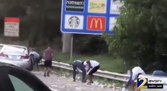 Drivers stop their vehicles and scramble to collect some of the cash that spilled onto the highway after the door of an armoured vehicle flew off while driving. PICTURE: Twitter/JackPosobiec