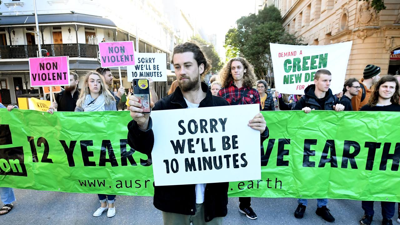 Extinction Rebellion protesters are seen blocking early morning peak hour traffic in Brisbane. Picture: AAP Image/Dave Hunt
