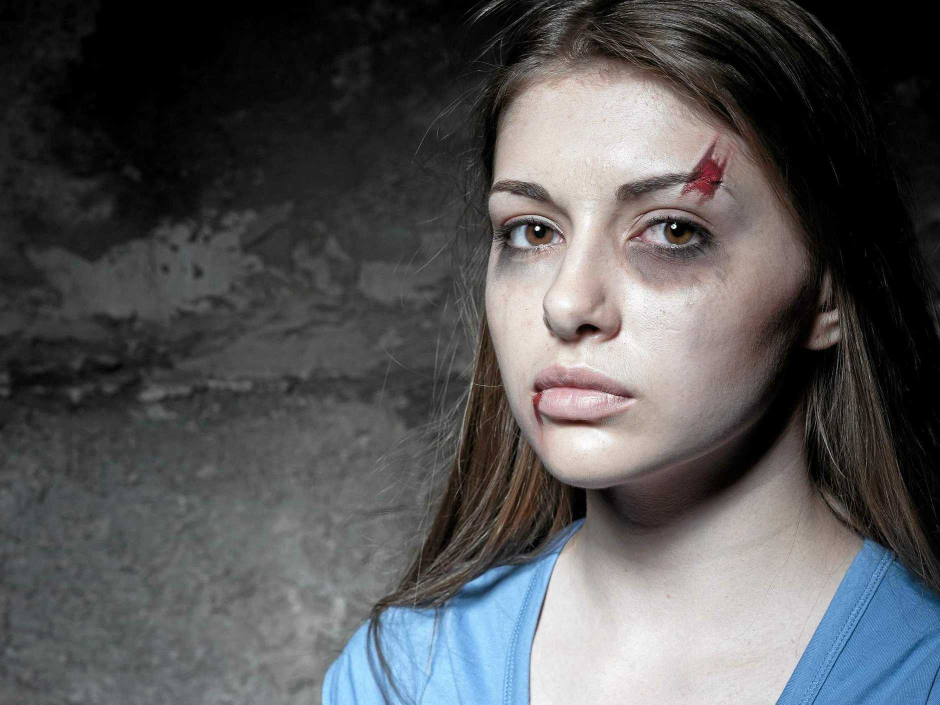 Young beaten up woman looking at camera while standing against dark wall