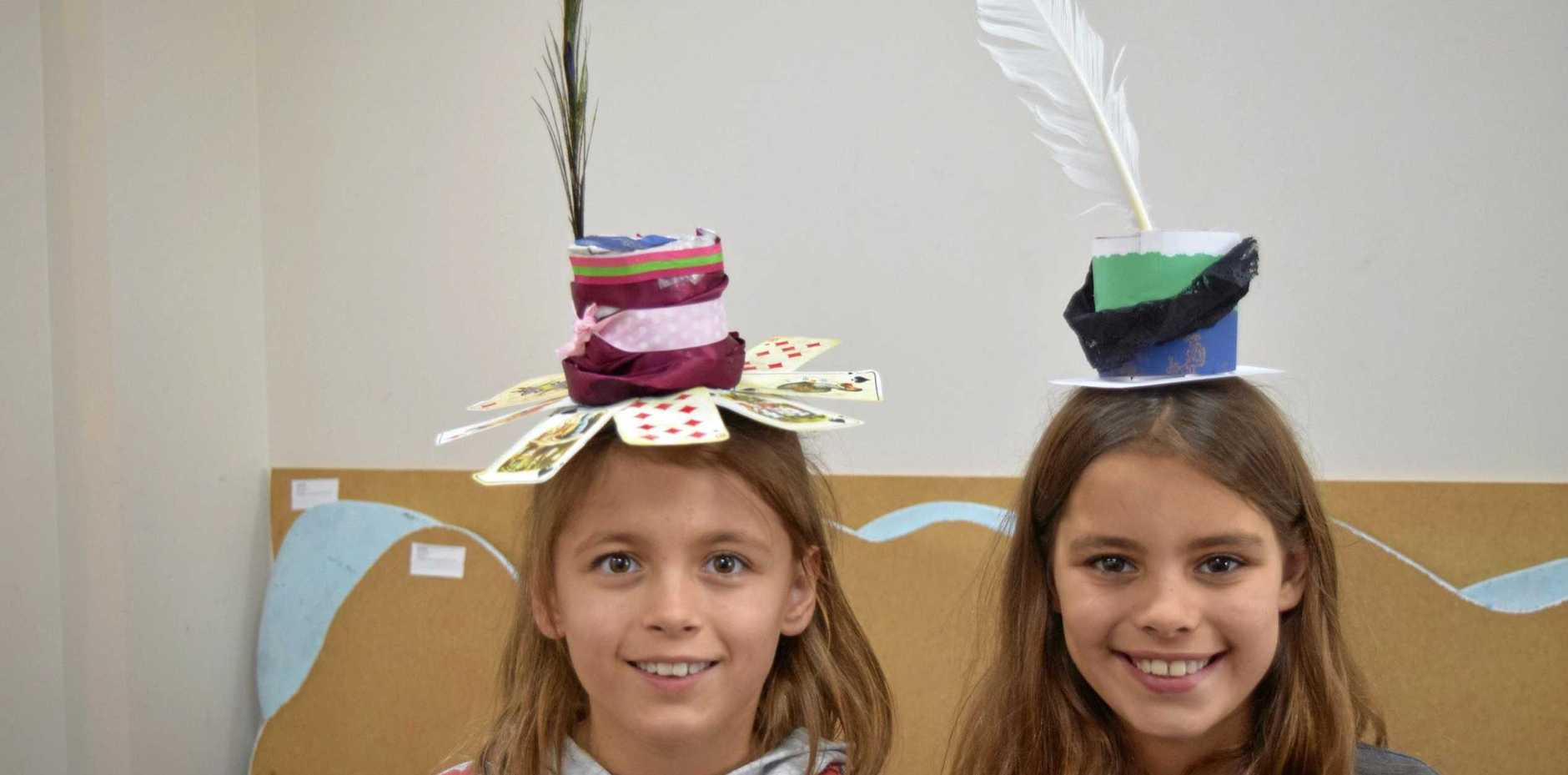 Woodwark twins Zahra Venter, 9, and Eloise Venter, 9, with the hats they made at the Mad Hatter's Tea Party at Cannonvale Library.