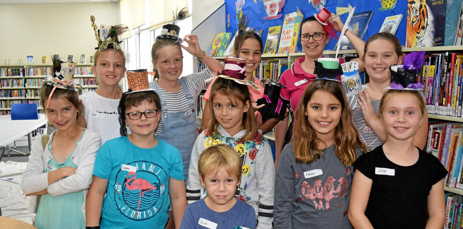 Some of the youngsters who attended the Mad Hatter's Tea Party at Cannonvale Library, show off their creations with Library assistant Anita Lichos.