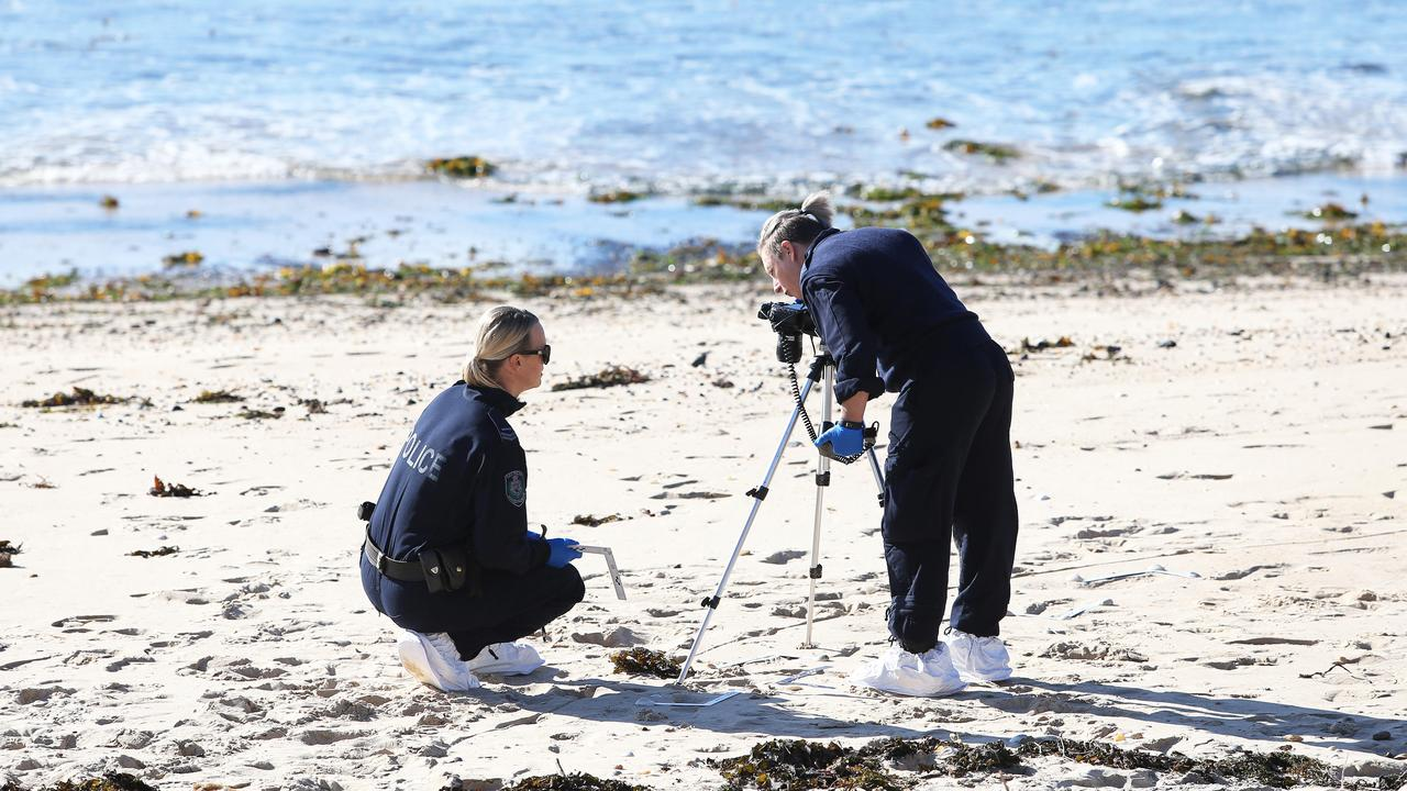 Forensic officers work at the crime scene on Stockton Beach where the man was found dead. Picture: Peter Lorimer
