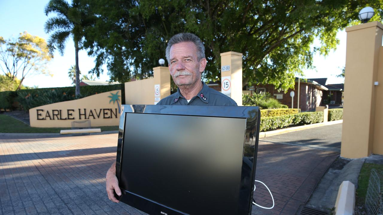 Lloyd Evans removes a TV that belongs to his mother in-law from Earle Haven at Nerang. Picture Glenn Hampson