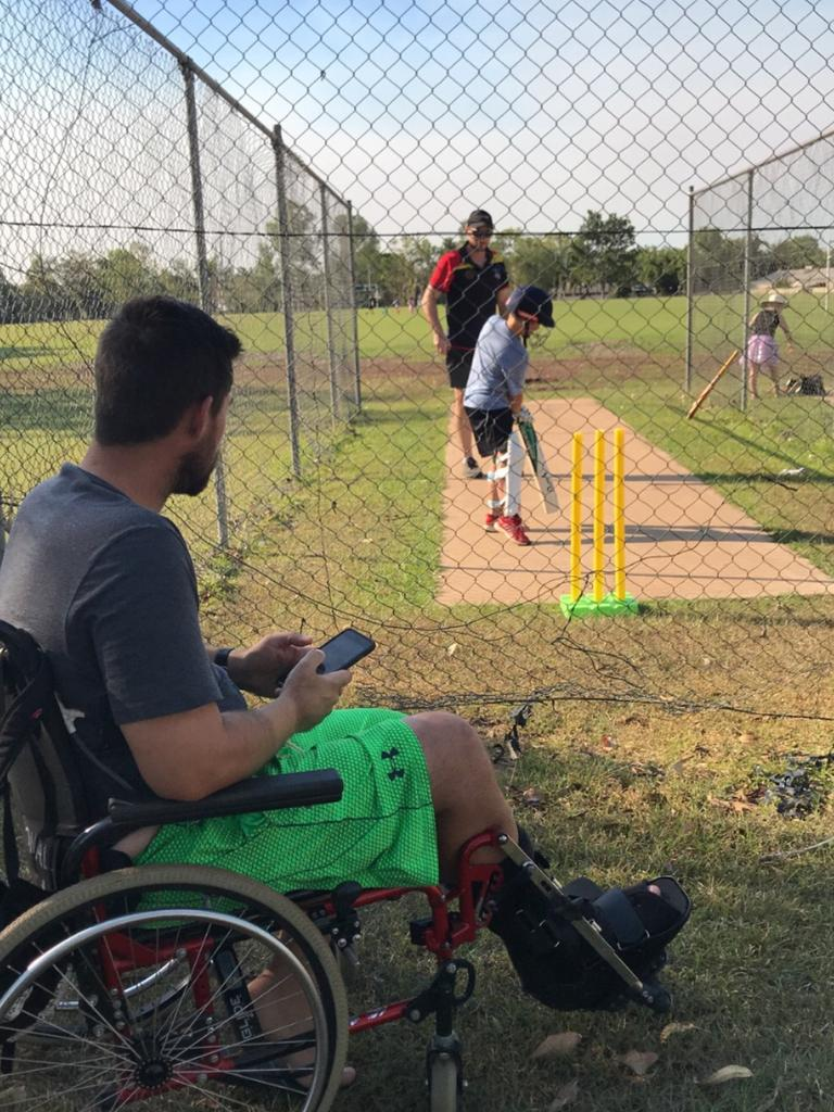 NT Police officer Senior Constable Jason Collingburn watching his son Cooper, 11, at cricket practice. He has undergone six surgeries to fight off a flesh eating disease