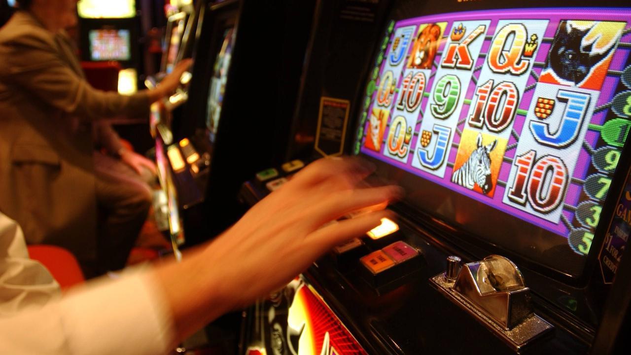 p39///12/08/2003. Unidentified person plays poker machine. Generic images of Tabcorp, TAB. gambling pokies gaming machine