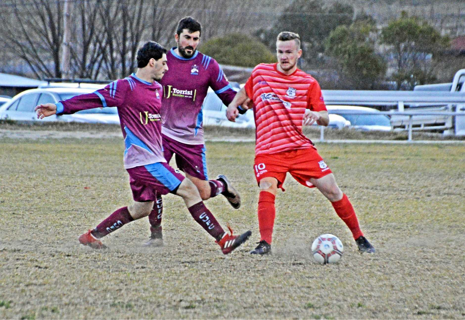 GET STUCK IN: Carlton's Michael Vaticano and Johnnie Torrisi try win the ball back off of Ballandean's Ben Rametta in the sides Saturday clash.