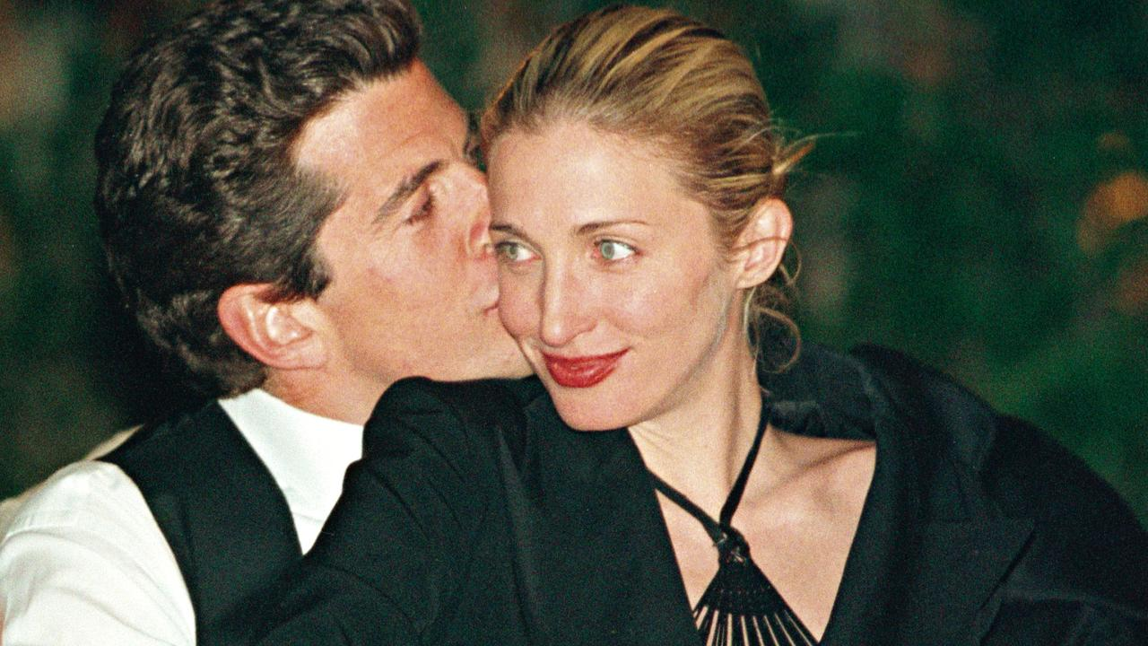 John F. Kennedy Jr. gives his wife Carolyn a kiss on the cheek during the annual White House Correspondents' dinner on May 1, 1999. The pair died in a plane crash along with Carolyn's sister Lauren 20 years ago. Picture: Getty Images