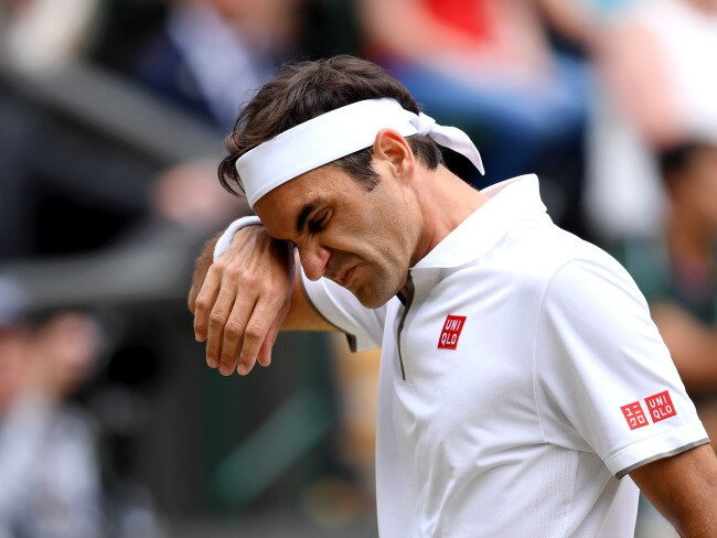 Roger Federer wipes sweat from his brow during the five-hour epic.