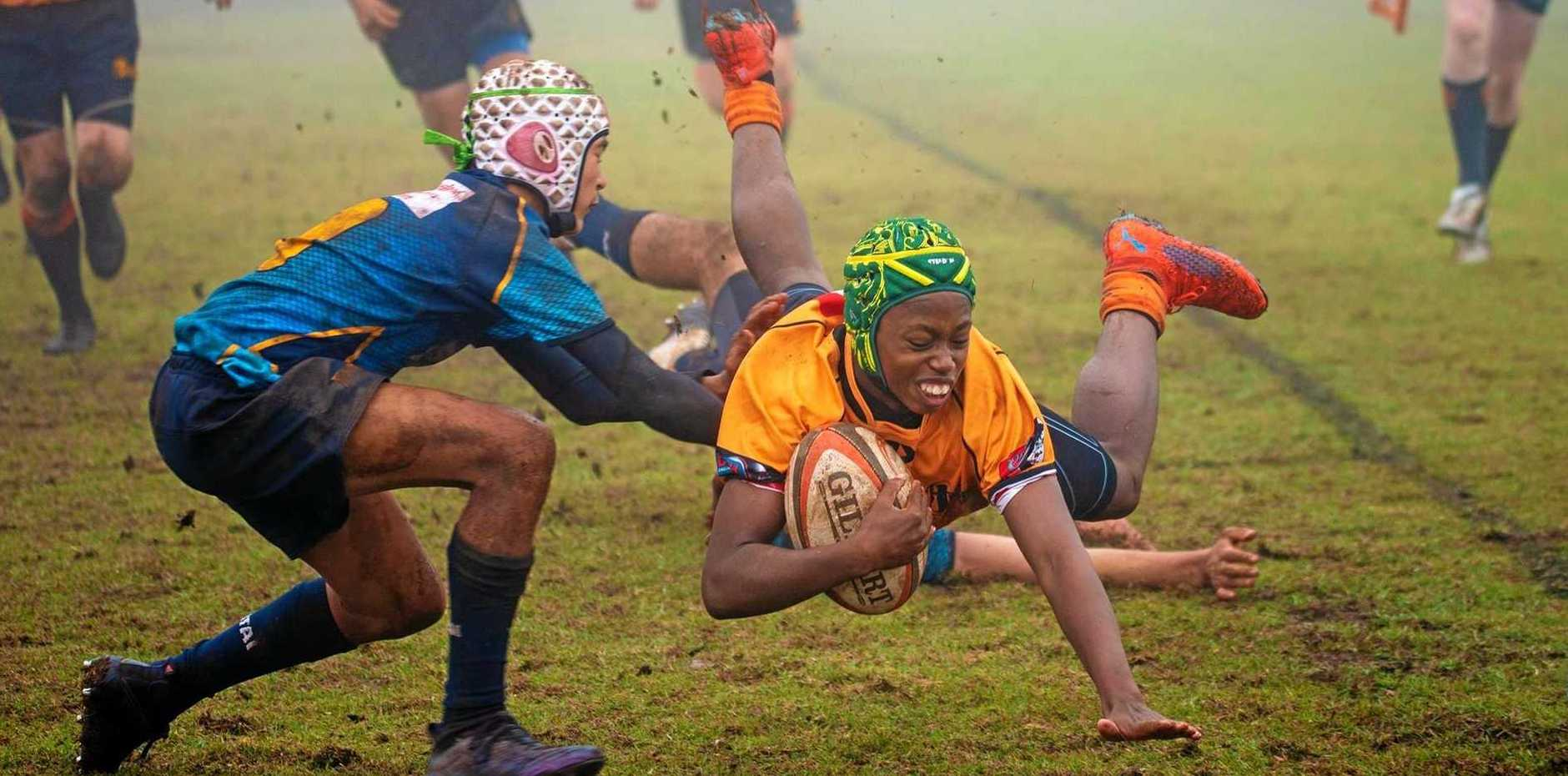 HOVERING: Nyasha Mhuka flies through for a try in the State Championship at Toowoomba.