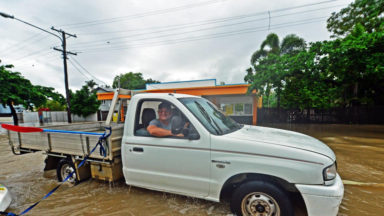 Des Smith is towed out of flood waters on Queens Road, Hermit Park. Picture: Zak Simmonds