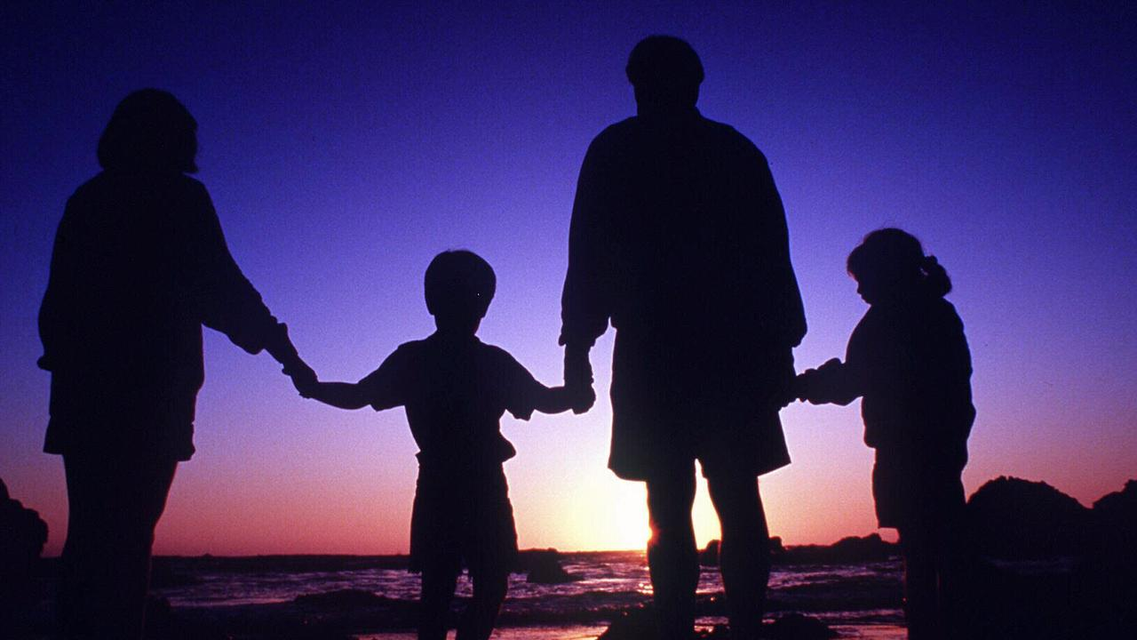Silhouette of family with parents and children holding hands at the beach.