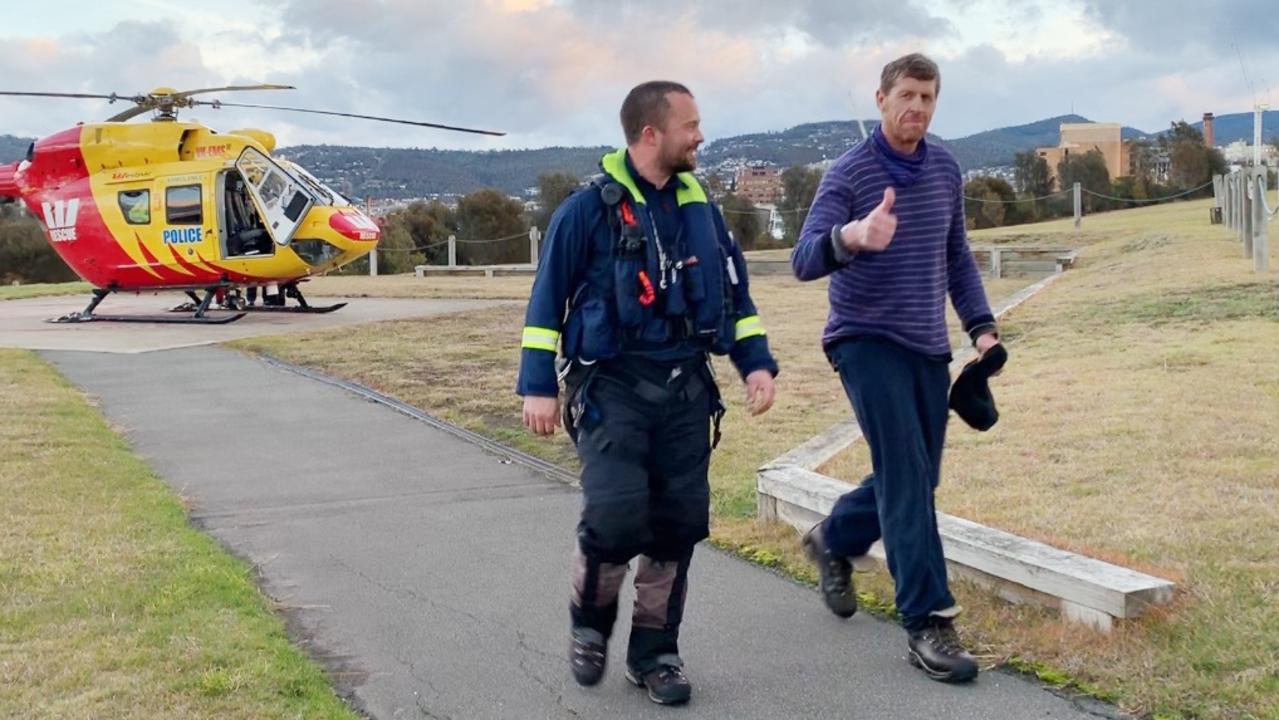Michael Bowman, 57, right, arrives in Hobart on the Westpac Rescue Helicopter after being found in the Cradle Mountain-Lake St Clair National Park. Picture: CHANEL KINNIBURGH
