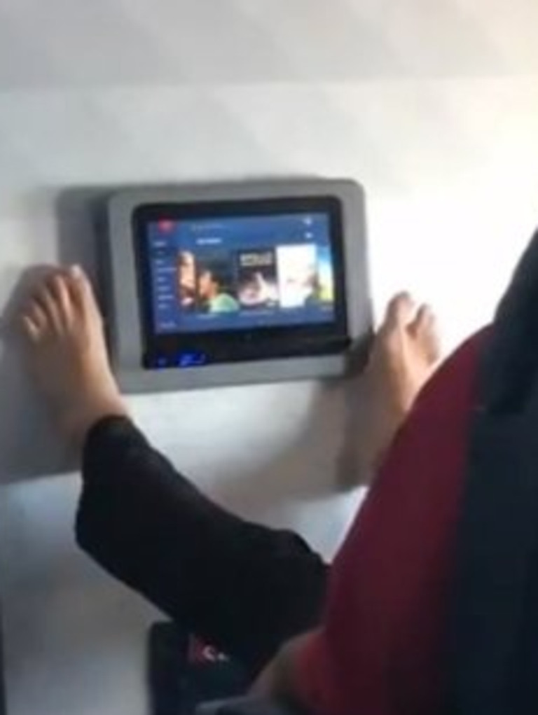 The passenger uses his feet on the screen