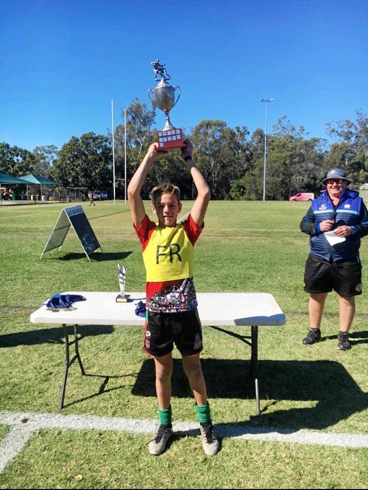 Emu Park under-12 captain Carter Welfare hoists the trophy high after his team won the Jason Hetherington Cup in Gladstone.
