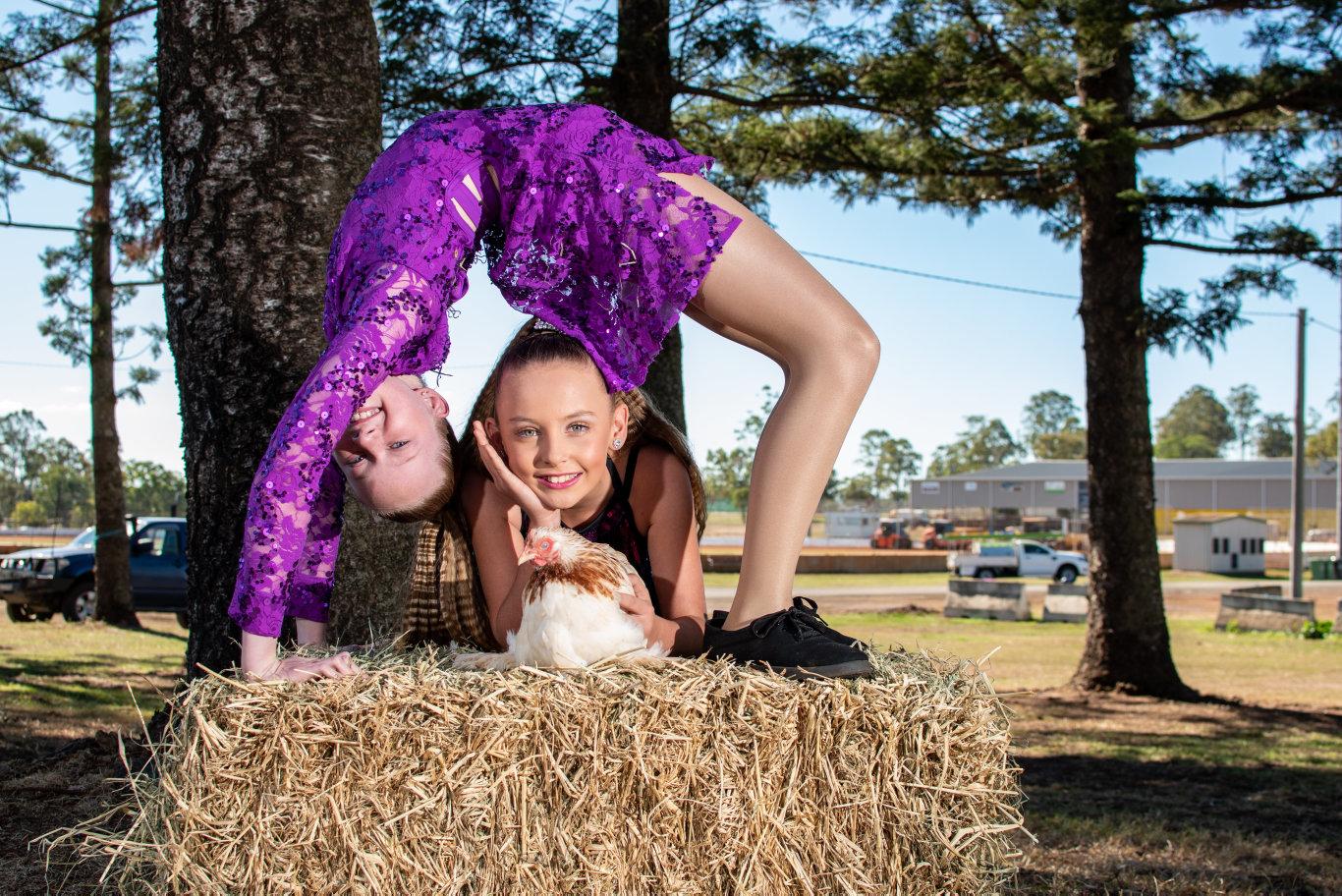 Starlite dancers Makenna Wakley, 10, of Mount Whitestone, holds her Salmon Peakin chicken Sally Salmon, with Hayley Shearer, 12, of Buaraba.