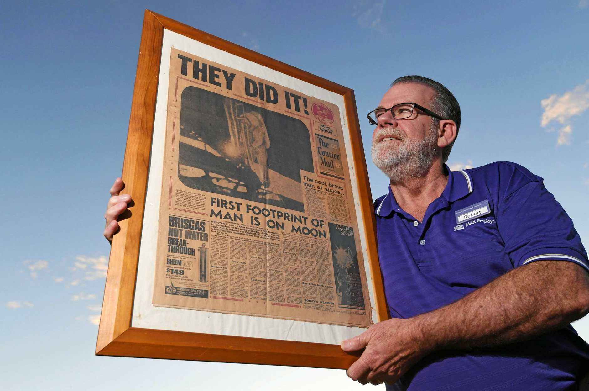 CAREER LAUNCHER: Robert Garland with his copy of the front page of  The Courier Mail  from the day after the landing.