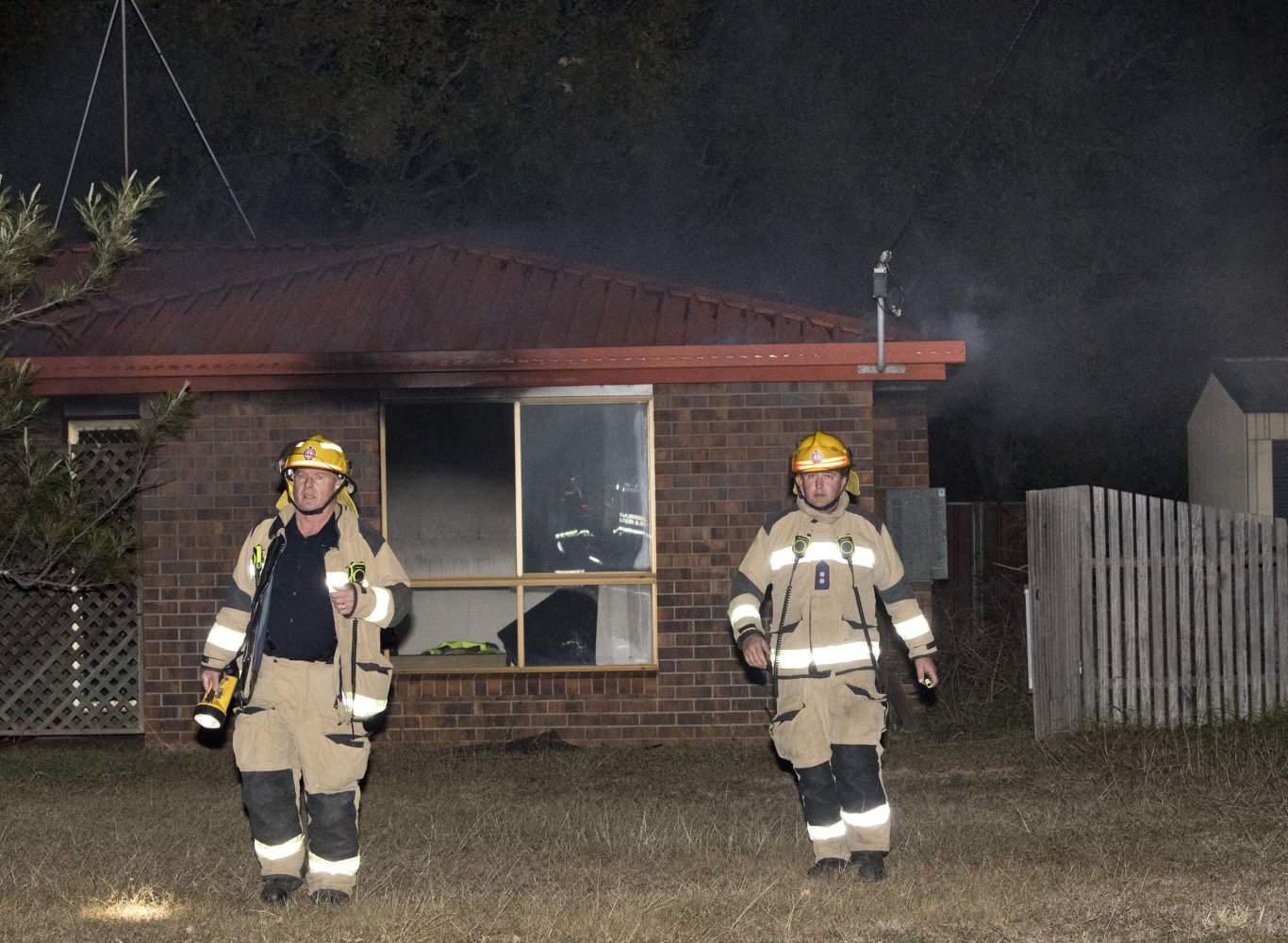 QFES Station Officer Scott Frame ( left ) investigates house fire in Blue Gum Drive, Newtown.