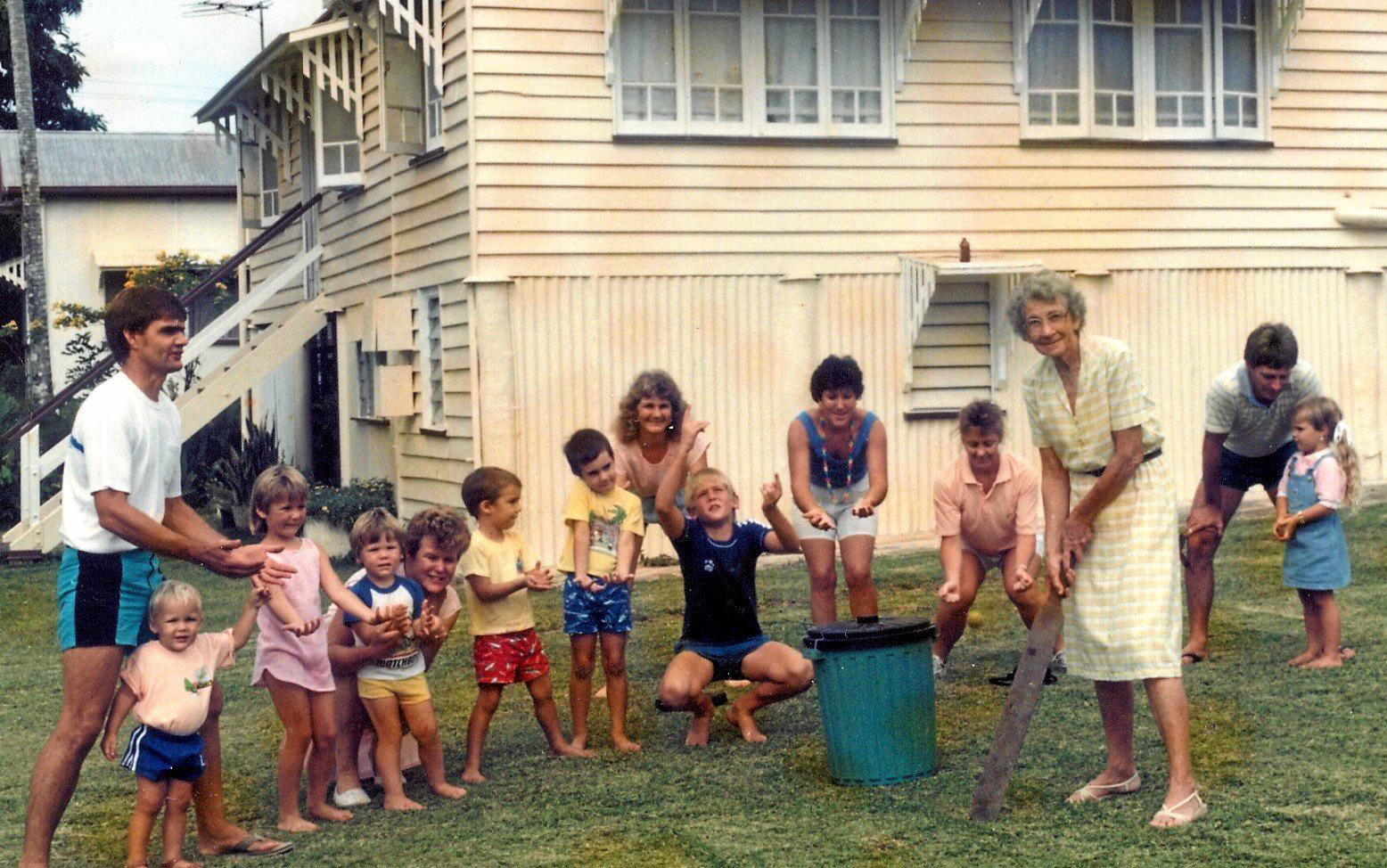 Doss Kerr playing cricket with some of her family in the backyard at 3 Atherton St Sarina. Son Alan (who lives at Mackay) is on left and his sister Leanne Kerr in middle with her husband Paul Buchanan on right. INSET BELOW LEFT: Gladys Petersen (wife of Stan Petersen of Petersen Bros butchery, Sarina) with Sarina Methodist Church children during a visit to Shinfield Methodist Church on Sarina Range during the early 1950s. Kerr boys Bill and David are standing on left. INSERT RIGHT: Bill Kerr (left) at the launch of Tin Town Triumph with Michael Jackes.