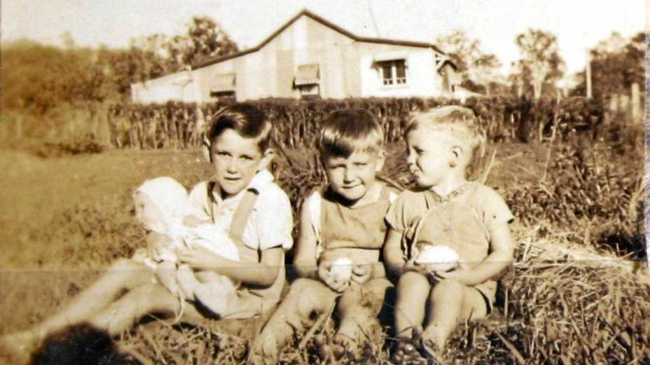 Brothers Robert (holding Ray), Bill and David Kerr in the 'tin town' in the late 1940s.