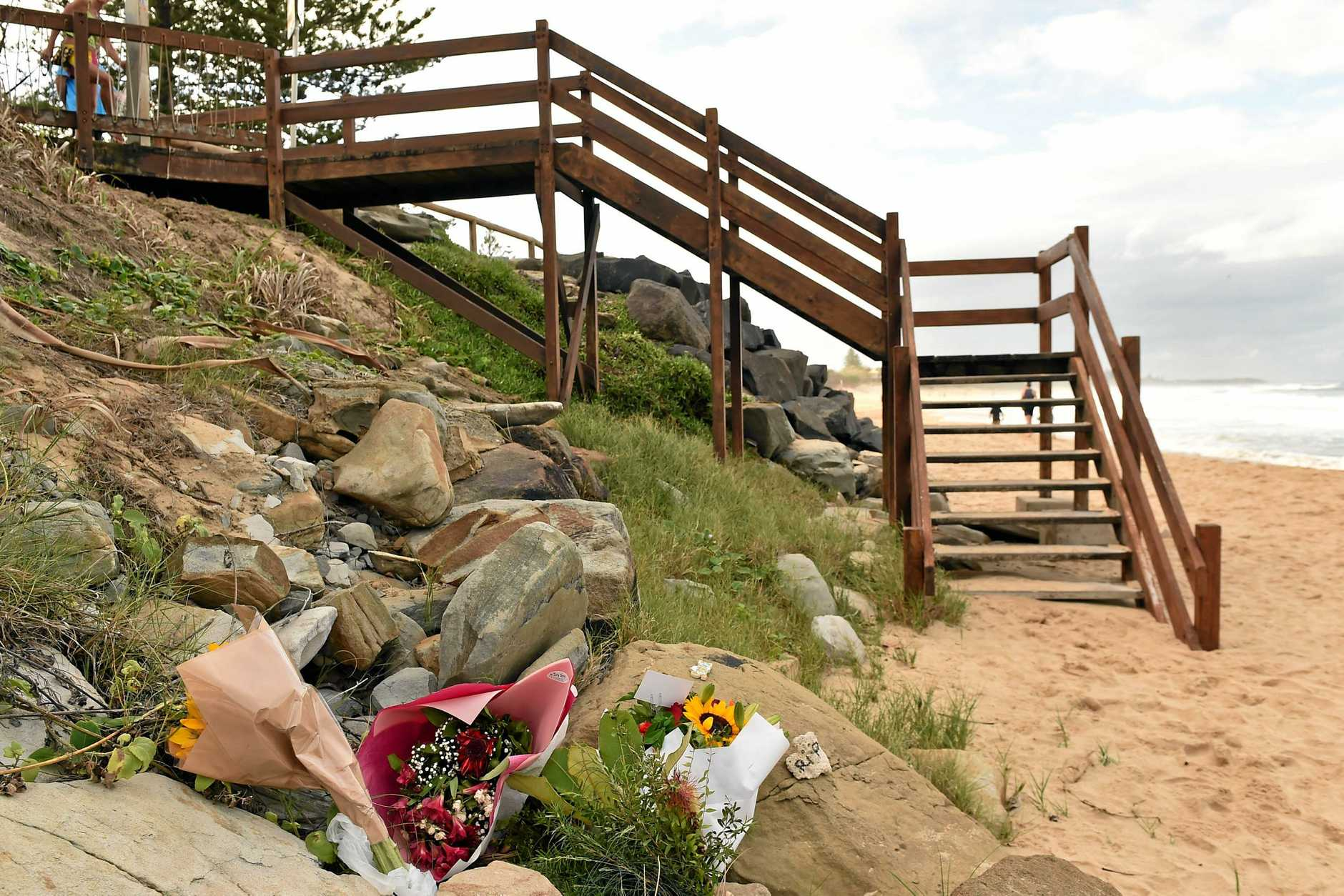 The Dicky Beach surfing community is reeling after the body of a young woman washed ashore. Flowers have been left at the botom of the staircase in her remembrance.