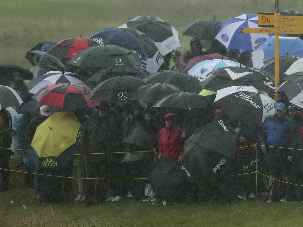 Spectators use umbrellas to shelter from the driving rain. (AP Photo/Jon Super)