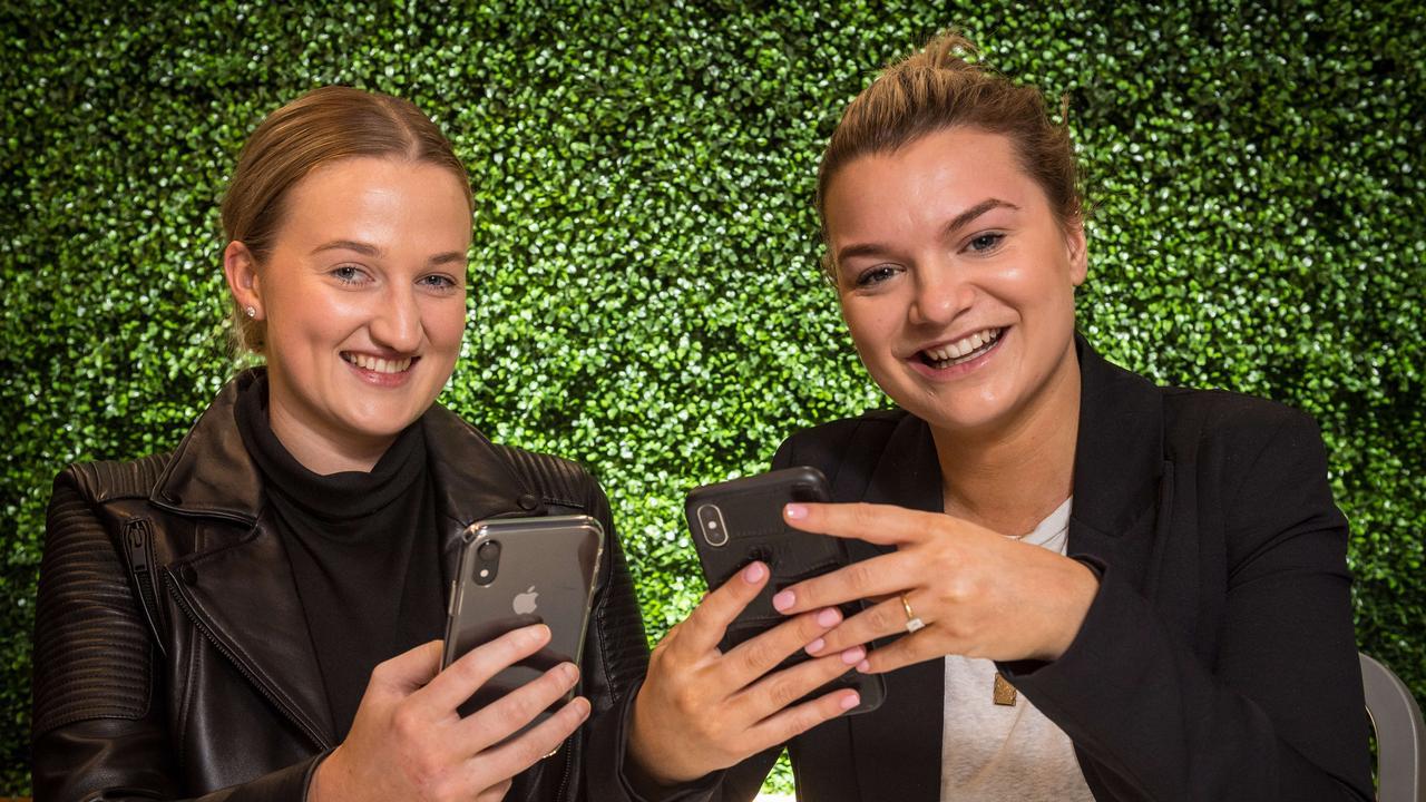 Eliza and Georgia on their phones. Picture: Jake Nowakowski