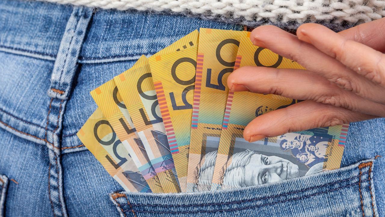 Female hand reaching for 50 Australian dollar bills in her jeans back pocket
