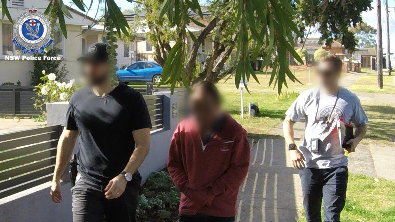 Police lead one of the arrested men away following the raids. Picture: NSW Police