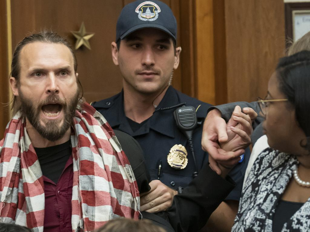 A protester shouts at former special counsel Robert Mueller as he arrived to testify to the House Judiciary Committee. Picture: AP