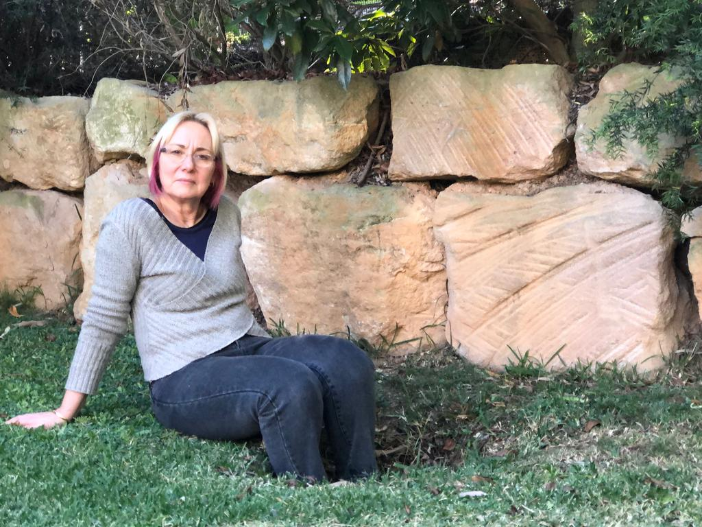 Christine le Poidevin with one of five sinkholes that appeared in her yard at Clayfield after the Airport Link tunnel was built.