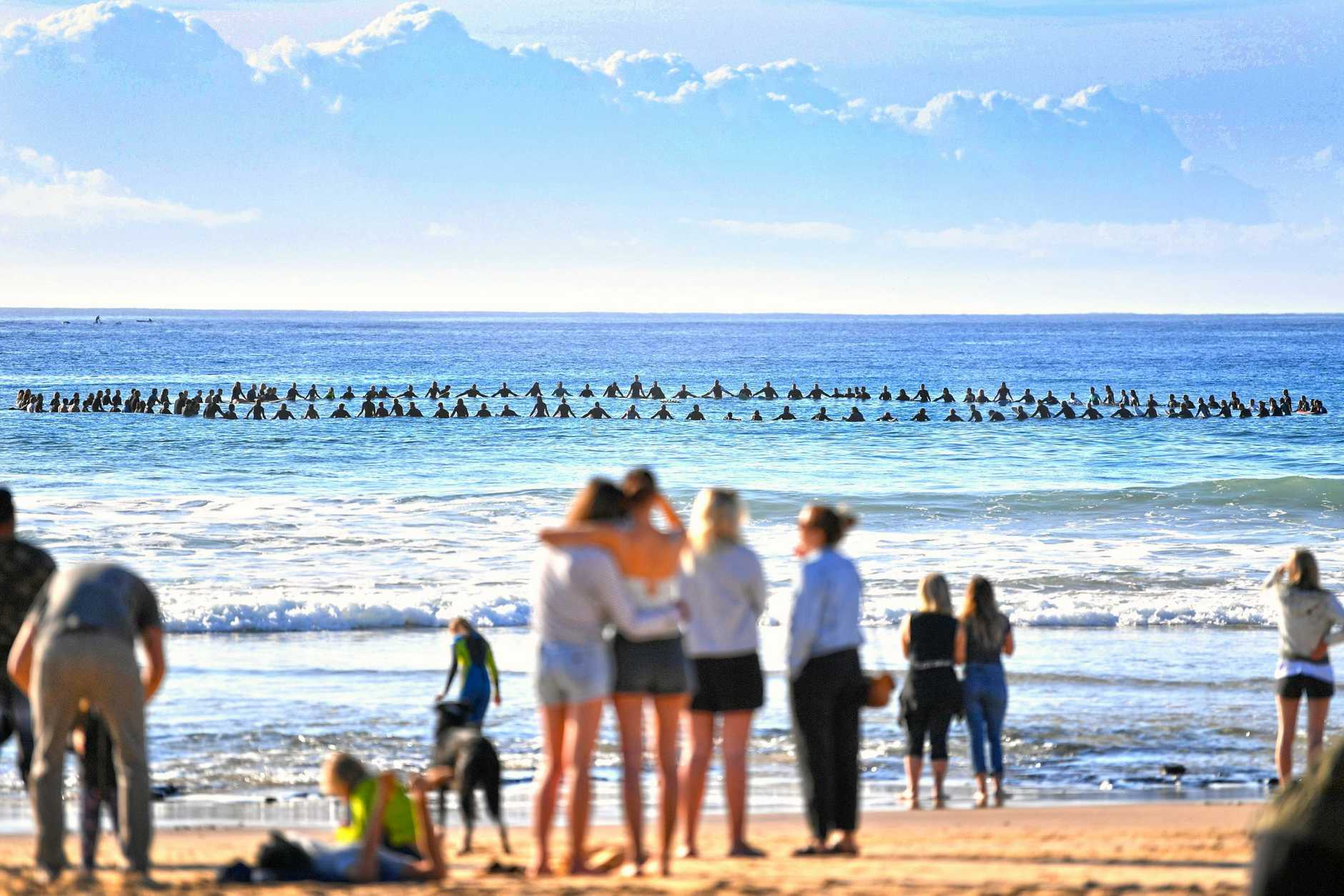 FAREWELL FOR A FRIEND: Hundreds gathered at Mudjimba Beach yesterday to paddle out in honour of Mike Daniell. Onlookers were touched as surfers formed a circle in the ocean for their friend.