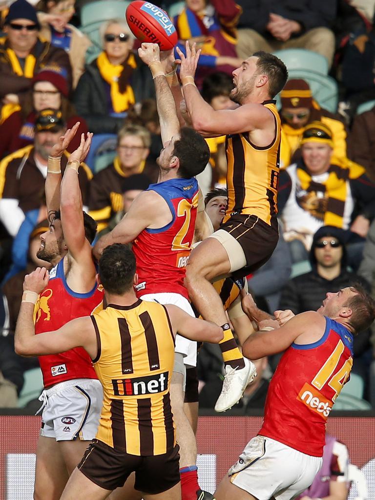 Hawks forward Jack Gunston flies for a mark over Lions defender Darcy Gardiner. Picture: Getty Images