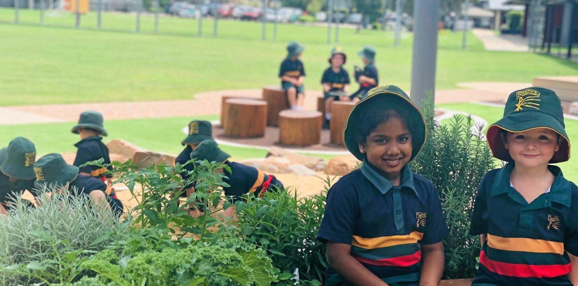 St Joseph's Catholic Primary School Students, Kaitlyn Silveira and William McKenna sit among one of their already vibrant school veggie gardens.