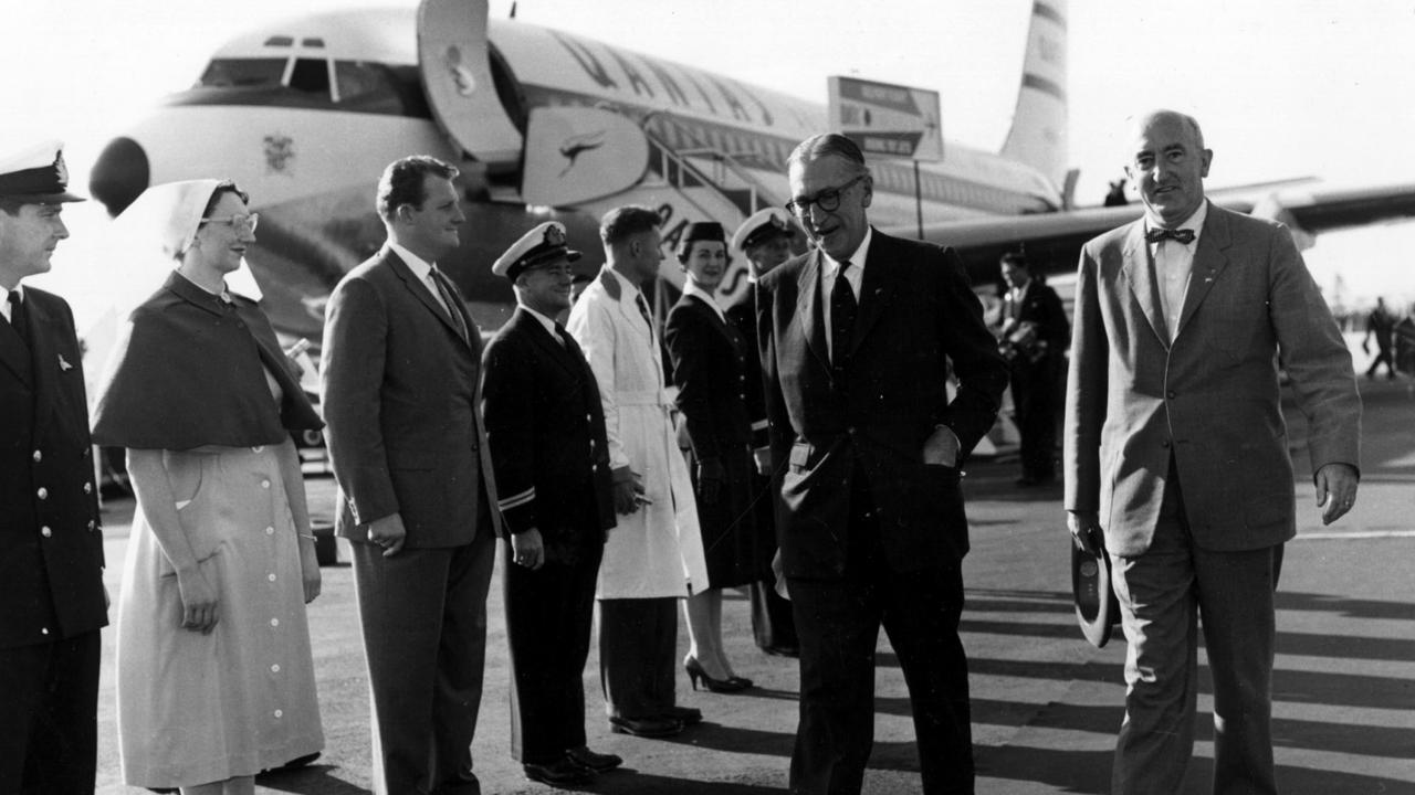 Sir Hudson Fysh (walking, on left) and Boeing Company present William Allen walk through a guard of honour representing every department in Qantas at the end of the first delivery flight from the US of Qantas's first Boeing 707 aircraft at Sydney Airport in 1959.