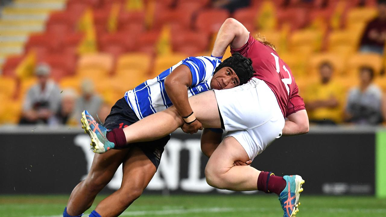 Eyzaiah Ulia of Nudgee College (left) tackles Wian Joubert of Brisbane State High. (AAP Image/Dan Peled)