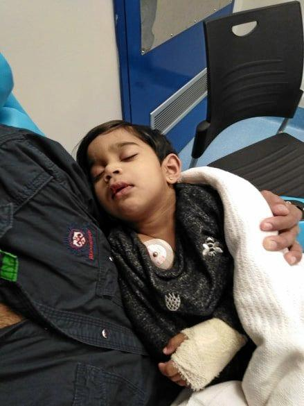 RECOVERY: Tharunicaa, 2, pictured in her father Nades' arms after she received surgery to have four rotten teeth removed.