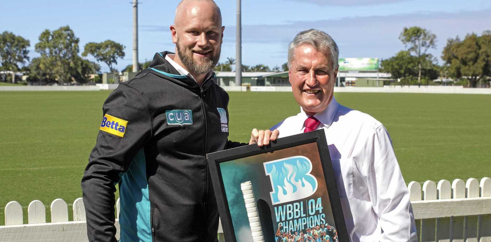 General manager of Brisbane Heat, Andrew McShea, handing over a signed bat from the 2018-19 WBBL winning team to Mackay Mayor Greg Williamson at Harrup Park.