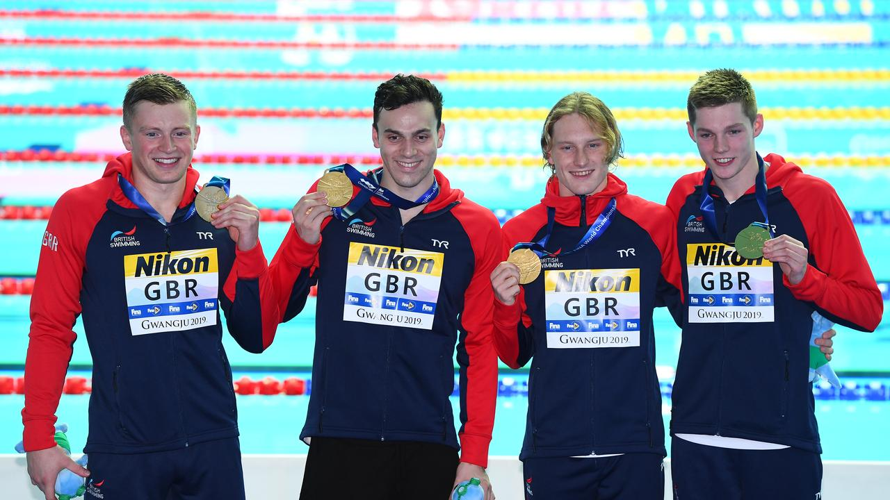Luke Greenbank, Adam Peaty, James Guy and Duncan Scott of Great Britain celebrate on the podium. (Photo by Quinn Rooney/Getty Images)