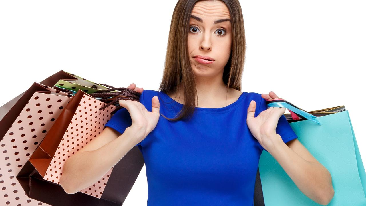 Portrait of young unhappy woman with shopping bags