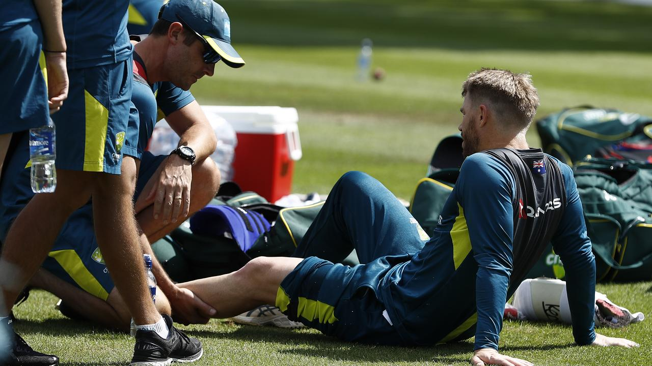 David Warner of Australia is assessed by Australian Team Physiotherapist David Beakley after being struck on the leg. Picture: Ryan Pierse/Getty Images