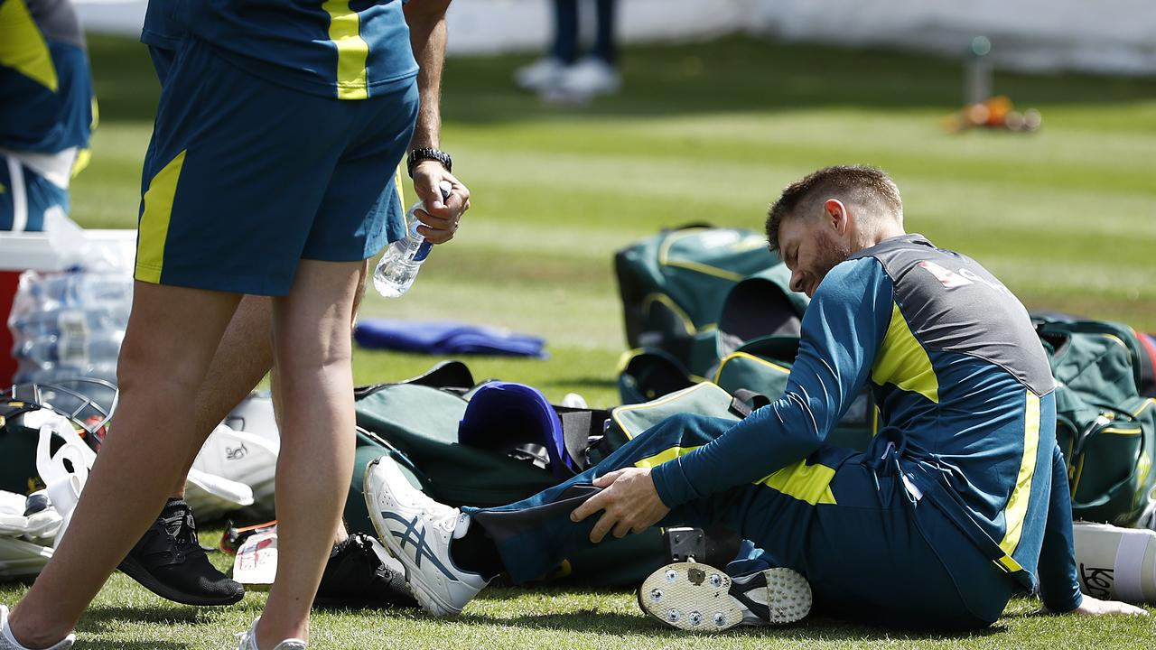 BIRMINGHAM, ENGLAND — JULY 29: David Warner of Australia is assessed by Australian Team Physiotherapist David Beakley after being struck on the leg during the Australia Nets Session at Edgbaston on July 29, 2019 in Birmingham, England. (Photo by Ryan Pierse/Getty Images)