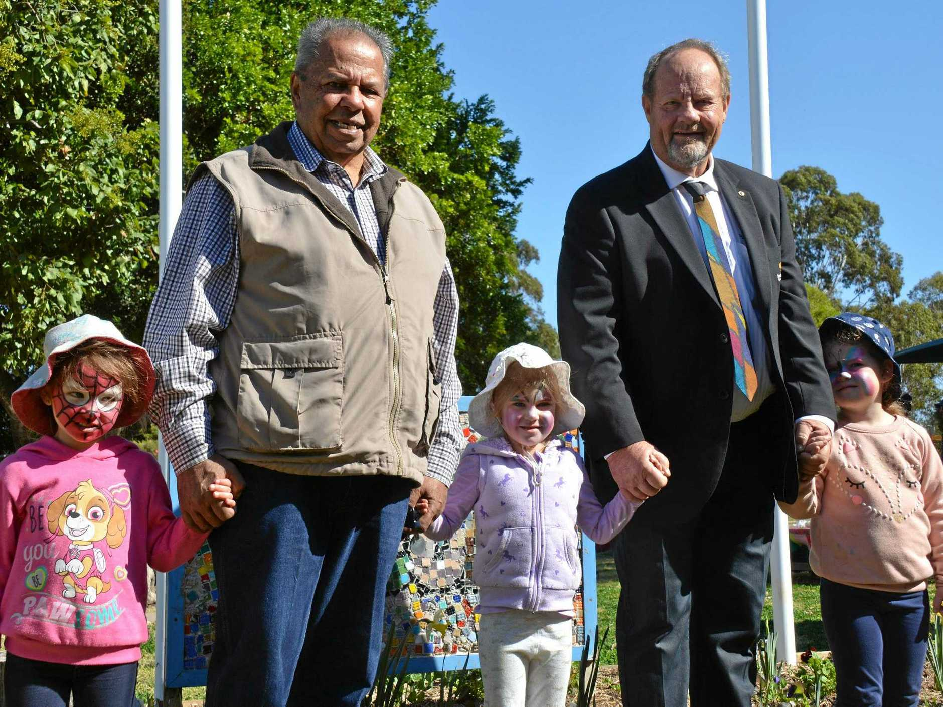NEW FLAGS: Kingaroy St John's Lutheran Kindergarten students Brooklyn Zischke, Juliete Fechner and Lucy Moseling with Cherbourg elder Eric Law and SBRC Cr Terry Fleischfresser unveil the flags.