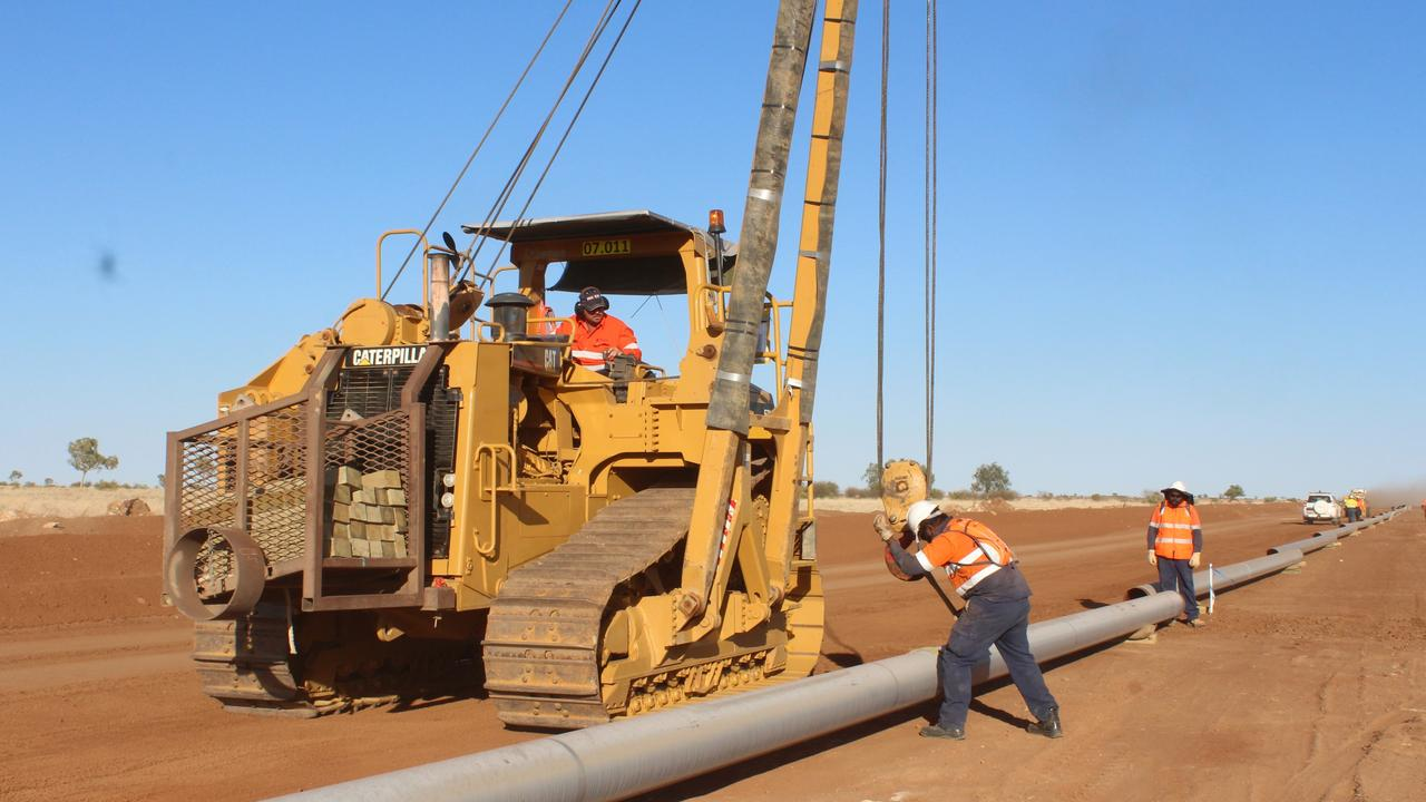 Workers install the pipe for Jemena's Tennant Creek to Mount Isa gas pipeline.