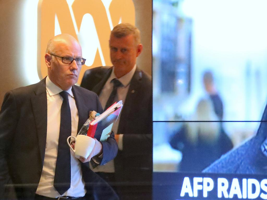 ABC News executive editor John Lyons, left, is followed by an Australian Federal Police officer in Sydney. Picture: AAP