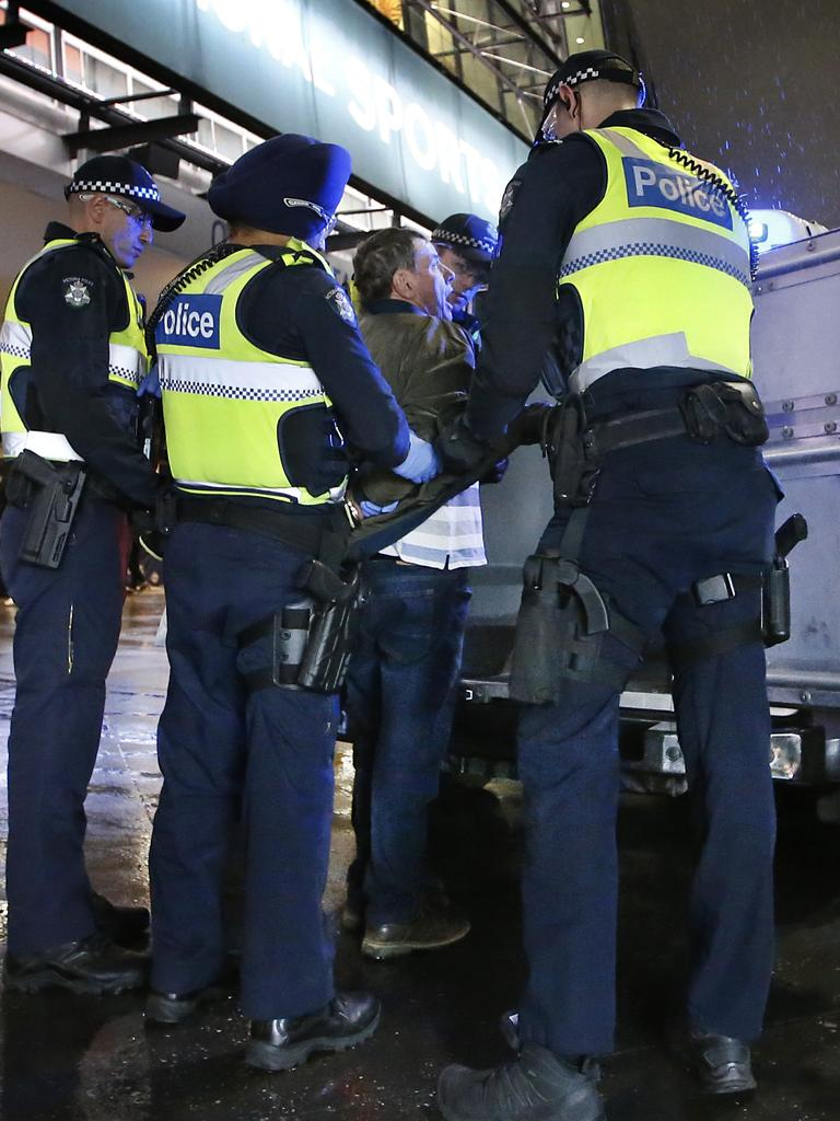 Police load a fan into a divvy van. Picture: David Caird