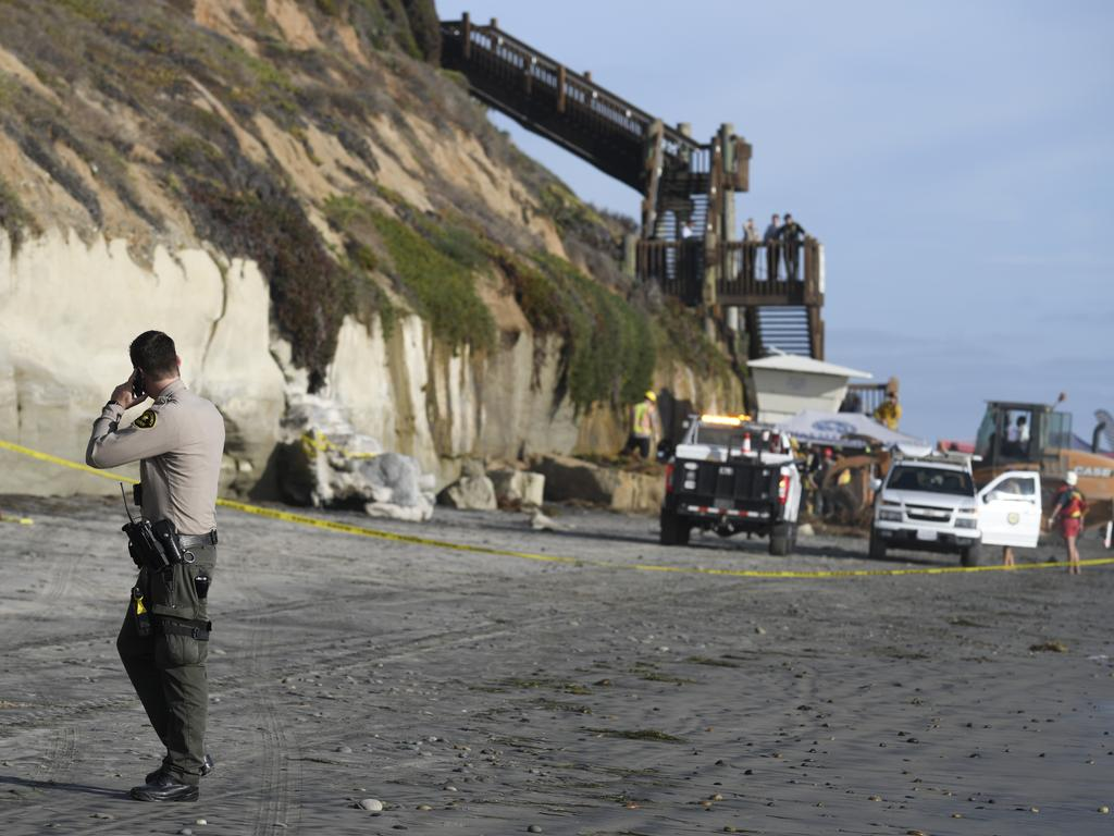 A San Diego County Sheriff's deputy looks on as search and rescue personnel work at the site of a cliff collapse at a popular beach in Encinitas, California. Picture: AP